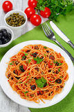 Spaghetti alla puttanesca with capers, top view. Spaghetti with tomato sauce, capers, anchovy and olives on plate with fork and knife on green table mat with Royalty Free Stock Image