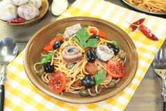 Spaghetti alla puttanesca with olives, capers and anchovies Stock Photos