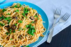Spaghetti Alla Puttanesca. Traditional italian pasta with black olives, tuna, anchovies, capers and parsley. Vegetarian food. Italian cuisine stock photography
