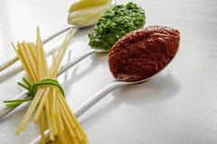 Free Spaghetti And Three Spoons With Different Condiments Stock Photo - 104193150