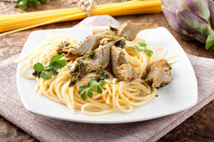 Spaghetti with artichokes and parsley Stock Photos