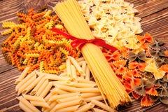 Spaghetti attachés avec un ruban rouge, un certain nombre de différents types de Photos stock