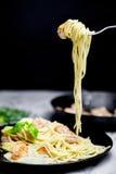Spaghetti avec des crevettes tournoyées sur la fourchette Photos libres de droits