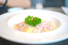 Spaghetti avec du jambon dans le plat blanc Images stock