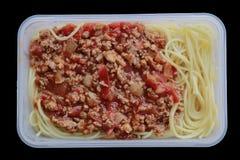 Spaghetti avec la boîte en plastique, sur le noir photographie stock