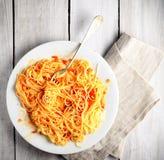 Spaghetti avec la sauce tomate sur un fond, une serviette et une fourchette en bois légers Image stock