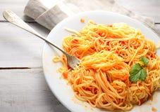 Spaghetti avec la sauce tomate sur un fond, une serviette et une fourchette en bois légers Images stock