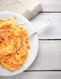Spaghetti avec la sauce tomate sur un fond, une serviette et une fourchette en bois légers Image libre de droits