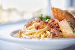 Spaghetti with bacon and garlic bread Stock Photo