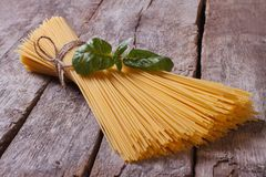 Spaghetti and basil on old table closeup. Ingredients for pasta Royalty Free Stock Photos