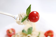 Spaghetti, basil and tomato on fork Royalty Free Stock Image