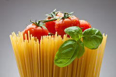 Spaghetti,Basil, Tomatoes. Close up of basic ingredients for italian pasta Royalty Free Stock Images