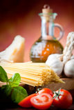 Spaghetti,Basil, Tomatoes. Raw pasta with tomato, basill, garlic, Parmesan cheese and olive oil close up Royalty Free Stock Photo