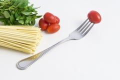 Spaghetti, basil and tomatoes. On white background Stock Image
