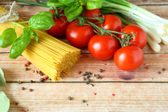 Spaghetti, basil and tomatoes on wooden background Royalty Free Stock Photo