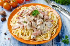 Spaghetti with Bechamel sauce, mushrooms and bacon Stock Images