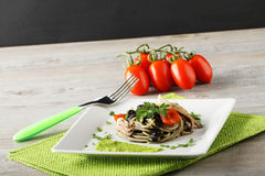 Spaghetti with black sepia, parsley and cherry tomatoes. On complex Background Royalty Free Stock Image