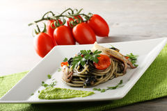Spaghetti with black sepia, parsley and cherry tomatoes. On complex Background Stock Photos