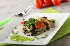 Spaghetti with black sepia, parsley and cherry tomatoes. On complex Background Stock Photo