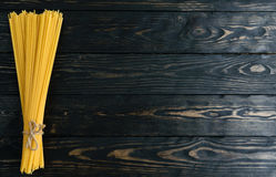 Spaghetti on black wooden background top view Stock Photo