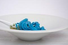 Spaghetti bleus, couvert noir Photographie stock libre de droits