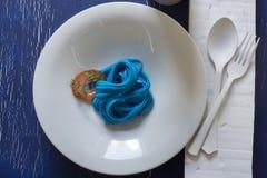 Spaghetti bleus, couvert noir Photographie stock