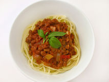 Spaghetti Bolognaise with Basil. Bowl of Spaghetti Bolognaise and basil on a white background Royalty Free Stock Photography