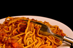 Spaghetti bolognese. A plate of spaghetti bolognese with a fork stock image