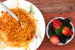 Spaghetti Bolognese and berry dessert Stock Images