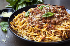 Spaghetti Bolognese. In black serving platter, with fresh basil and parmesan Royalty Free Stock Image