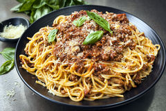 Spaghetti Bolognese. In black serving platter, with fresh basil and parmesan Stock Image