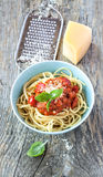 Spaghetti bolognese in blue bowl on vintage rustic wood. Spaghetti bolognese with parmesan and basil in a blue bowl on vintage rustic wooden table - italian food Royalty Free Stock Images