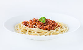 Spaghetti bolognese. Decorated with coriander leaf on a white plate and on white background Stock Images