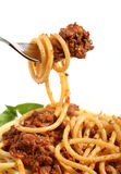 Spaghetti bolognese on a fork. A fork lifting spaghetti bolognese above a plate of the same Stock Photos