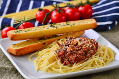 Spaghetti bolognese with garlic bead baguettes. Royalty Free Stock Photos