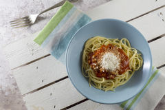 Spaghetti bolognese with grated cheese on blue plate Stock Image