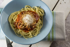 Spaghetti bolognese with grated cheese on blue plate Stock Images