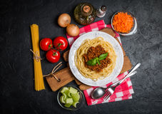 Spaghetti bolognese with ingredients. On black background. Top view with copy space Royalty Free Stock Photography