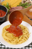 Making Italian spaghetti bolognese with pouring sauce and ingredients, vertical. Bowl of spaghetti bolognese with ingredients in the background Stock Photos