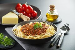 Spaghetti bolognese meal. Delicious spaghetti with bolognese sauce served on a black plate stock photography