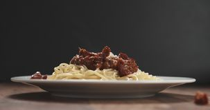 Spaghetti bolognese with parmesan and sundried tomatoes on plate on table Stock Images