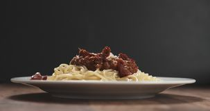 Spaghetti bolognese with parmesan and sundried tomatoes on plate on table Stock Photo