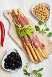 Grissini. Bread sticks with ham, olives, fresh oregano herbs and peanuts royalty free stock images