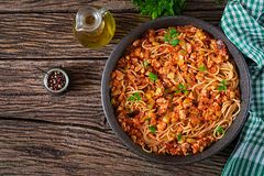 Spaghetti bolognese pasta with tomato sauce, vegetables and minced meat. Homemade healthy italian pasta on rustic wooden background. Top view. Flat lay royalty free stock image