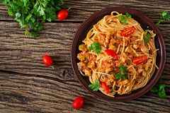 Spaghetti bolognese pasta with tomato sauce, vegetables and minced meat. Homemade healthy italian pasta on rustic wooden background. Top view. Flat lay royalty free stock photo