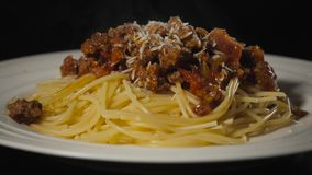 Spaghetti with bolognese sauce on the black isolated background, serving, huge big stock video