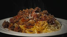 Spaghetti with bolognese sauce on the black isolated background, serving, huge big stock video footage