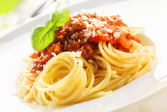 Spaghetti with Bolognese sauce. Closeup of coiled cooked Italian spaghetti topped with Bolognese sauce and garnished with fresh basil leaves Stock Images