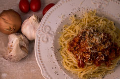 Spaghetti with bolognese sauce and parmesan. In plate on wooden table, with garlic, onion and spoon Royalty Free Stock Images