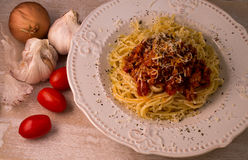 Spaghetti with bolognese sauce and parmesan. In plate on wooden table, with garlic, onion and tomatoes royalty free stock photography